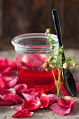 Rose jelly in a jar next to a spoon and rose petals
