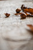 Chestnuts with leaves on a wooden surface