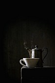Alte Kaffeekanne und weisse Tasse auf schwarzem Tisch