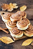 A stack of cinnamon buns on a chopping board