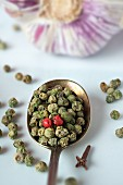 Green and pink peppercorns on a spoon with a garlic bulb in the background
