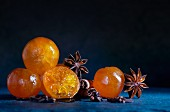 Candied clementines with star anise and cinnamon sticks on a blue slate surface