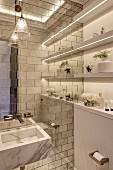 Elegantes Bad mit Marmor Waschbecken an gefliester Wand, seitlich Ablagen mit integriertem Lichtband