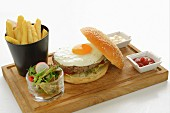 A hamburger with a fried egg served with chips, salad, ketchup and mayonnaise