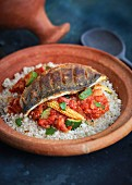 Tagine with a tomato and vegetables sauce and fish