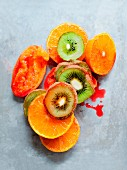 Kiwi slices, halved oranges and juiced blood oranges (seen from above)