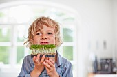 A little boy in a kitchen holding fresh cress