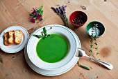 Green herb soup, bread, salt, pepper and fresh herbs