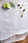 Caper fruits, a sprig of dill and limes on a piece of white paper