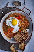 A fried egg on ratatouille with grilled bread