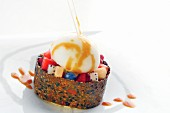 Exotic fruit salad in a ring of seed brittle with creamy ice cream and caramel sauce