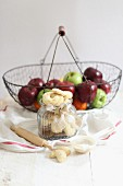 Vanilla cresent biscuits in jar and apples in a wire basket