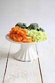 Grated vegetables on a white cake stand