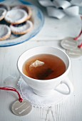 A cup of tea with a tea bag with a plate of biscuits in the background