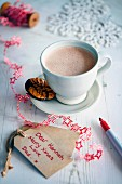 A cup of hot chocolate next to Christmas gift tags