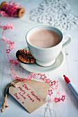 Eine Tasse heißer Kakao daneben weihnachtlicher Geschenkanhänger