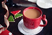 A cup of tea with milk next to Christmas decorations