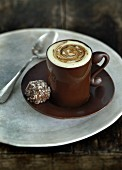 A cup of coffee and a praline