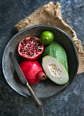 Pomegranate, vegetable papaya and a lime in a bowl with a knife