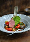 A rack of lamb with a herb crust on a bed of ratatouille