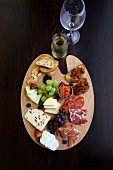 A supper platter with cheese, ham, crostini and grapes