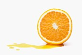 Half and orange with juice running out on a white surface