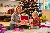 Zwei Kinder beim Auspacken von Weihnachtsgeschenken vor Christbaum