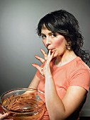 A young woman licking chocolate from her fingers