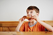 A boy sitting at a table biting into a slice of bread