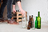 Mann stellt leere Flaschen in Holzkiste