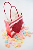 A gift bag decorated with a heart surrounded by heart-shaped sweets