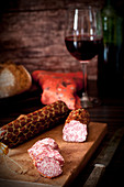 Smoked red wine salami made from pork and beef on a wooden chopping board