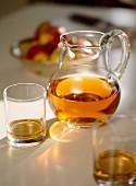 Apfelsaft in Glaskrug und Gläsern im Sonnenlicht vor einer Schale mit frischen Äpfeln
