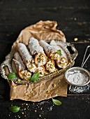 Cannoli with icing sugar and pistachio nuts