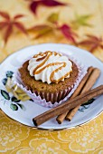 A pear and spice cupcake with cream cheese frosting and caramel