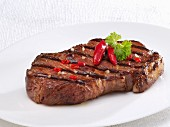 A fried beef steak with chilli peppers