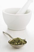 Dried oregano on a spoon in front of a mortar