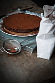 Chocolate tart on a metal tray with utensils for dusting cocoa powder on wooden table