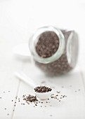 Chia seeds on a spoon and in a storage jar