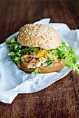 A salmon burger with green lettuce, onions and sauce