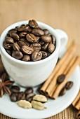 Kaffeebohnen in einer Tasse mit Gewürzen
