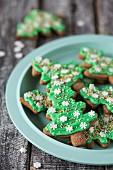 Lebkuchen-Weihnachtsbaum-Cookies mit grüner Zuckerglasur auf Teller