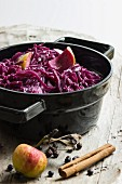 Red cabbage with apples, cinnamon and juniper berries in a back pot on a wooden board