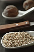 White sesame seeds on a porcelain spoon