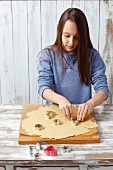 A little girl cutting out biscuits