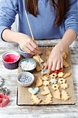 A girl decorating homemade Christmas biscuits
