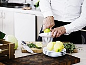 A man in a kitchen juicing lemons and limes