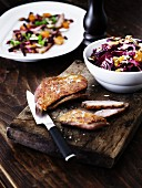 Sliced duck breast and winter red cabbage salad on a wooden board