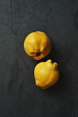Two fresh quinces on a grey surface (seen from above)