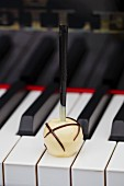 A white chocolate praline on the keys of a piano